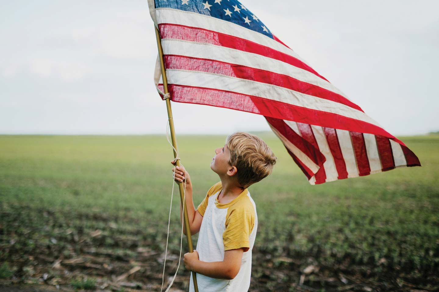 child holding an American Flag in a field